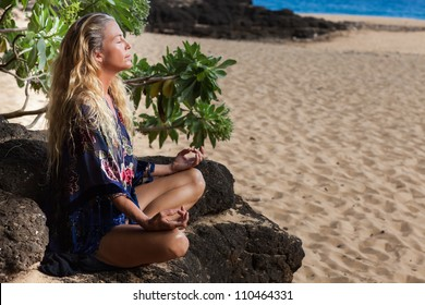 Pretty Woman with long hair in her Forties Meditating in Hawaii on a Lava bed at the Beach