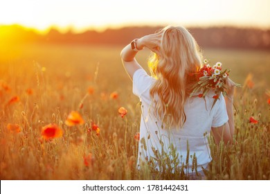 Pretty woman with long hair on poppy field at sunset. Back view. Fashion outdoor photo of beautiful  flying blonde  hair. Close up picture
