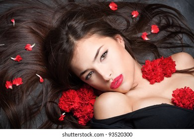 Pretty woman with long hair and red carnations