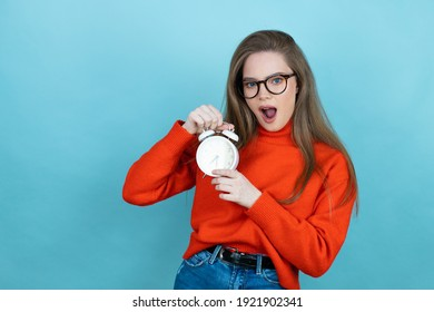 Pretty woman with long hair wearing a casual sweater and glasses over blue background screaming and scared, pointing the clock