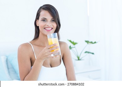 Pretty woman looking at camera holding glass of juice at home