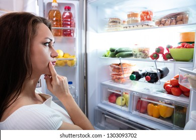 Pretty Woman Looking For Food In Refrigerator
