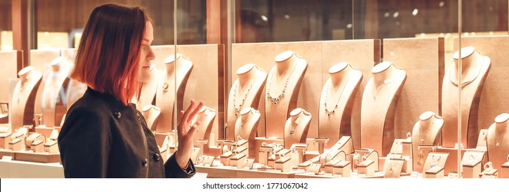 Pretty woman looking at jewelry in store window. Customer near jewellery. Dreamy red hair girl chooses silver, gold, diamonds, precious stones. Banner