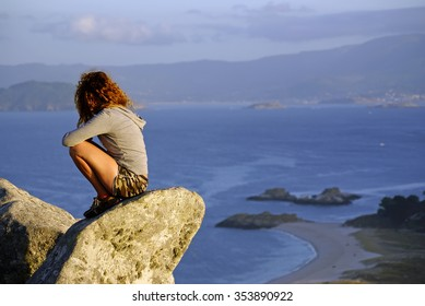 A pretty woman looking at the landscape of a beach, on top of a mountain at sunset,