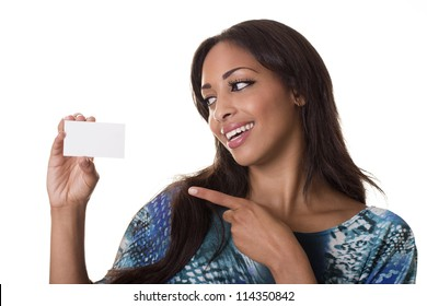 A pretty woman looks at a blank business card while pointing at it.