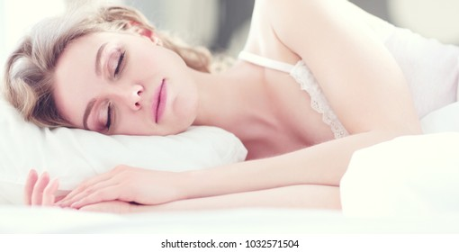 Pretty woman lying down on her bed at home.