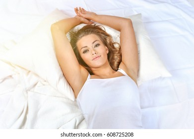 Pretty woman lying down on her bed at home waking up in the morning