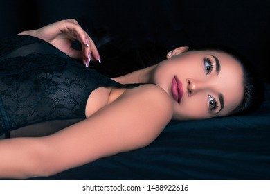 Pretty woman lying on black sheets