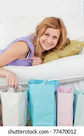Pretty woman lying on the couch with her shopping bags in the living-room