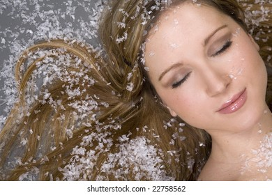 pretty woman lying on snow and grey background