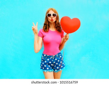 Pretty woman makes an air kiss holds a red balloon in the shape of heart on blue background
