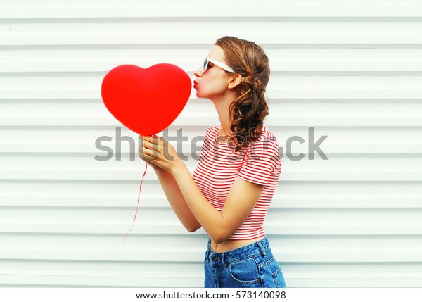 pretty woman making air kiss with red balloons heart shape over white background