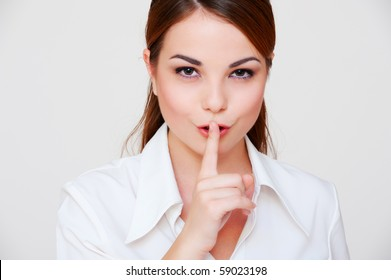 pretty woman making silence sign over grey background