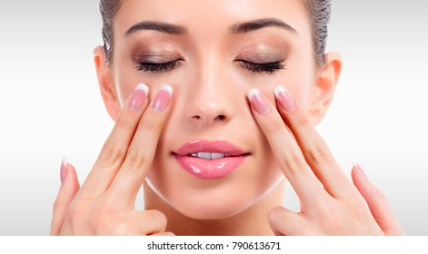 Pretty woman massaging her face against a grey background with copyspace