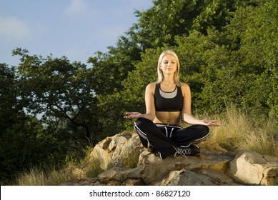 Pretty woman meditating on rock eyes closed with gold light reflector