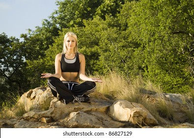 Pretty woman meditating on rock open hands with gold light reflector