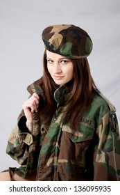 Pretty woman in a military camouflage jacket and beret hat, looking at the camera with a friendly, sexy smile and holding the lapel of her jacket