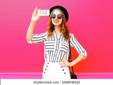 Pretty woman model taking picture self portrait on smartphone wearing black hat white pants over colorful pink background