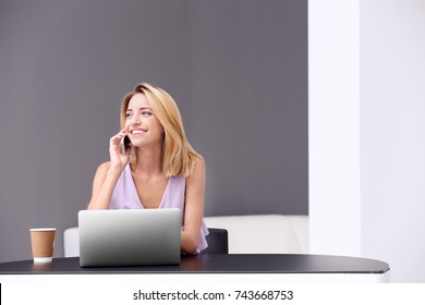 Pretty woman with modern laptop talking by phone at home