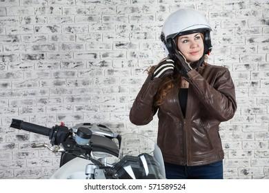 Pretty woman a motorbiker wearing open white helmet near her motorbike in garage, brick wall background