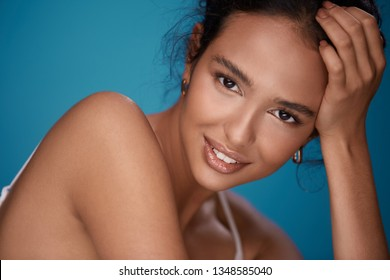 Pretty woman with naked shoulders, curly hair and nude make up smiling at blue background, perfect smile, close up.