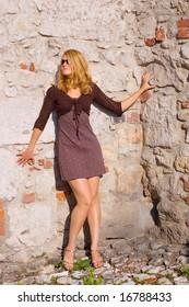 Pretty woman near the ancient brick wall