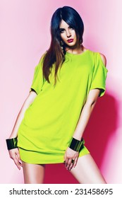 pretty woman in neon green dress with pink lips in studio