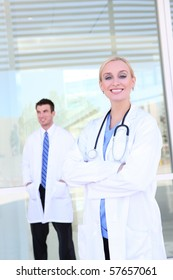 Pretty woman nurse/doctor smiling in front of hospital with man in background