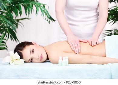 Pretty woman on back massage in spa center