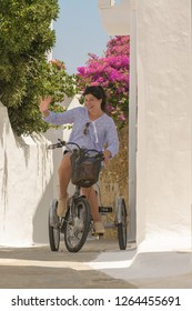 Pretty woman on a bicycle at Andros island in Greece on her vacation time.