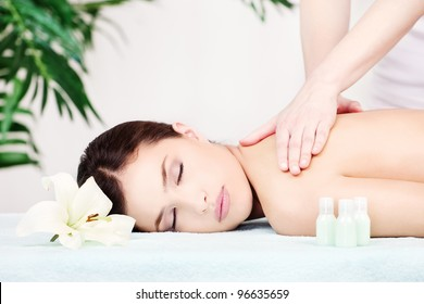 Pretty woman on shoulder massage in salon