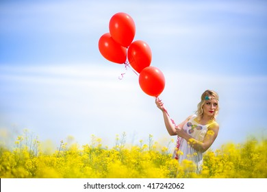 Pretty woman on a yellow flower field with balloons