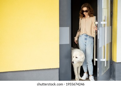 Pretty woman opens the door of entrance of the building and goes for a walk with the dog in the courtyard of the residence. Animal lover, pet friendly owner.