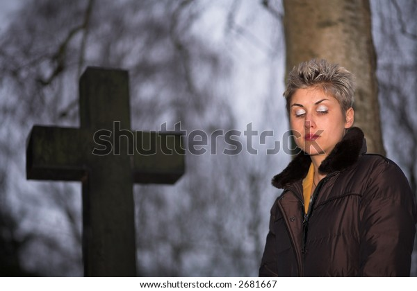 pretty woman outdoor in a cemetery fronting a grave with a cross -  in denmark