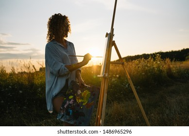Pretty woman is painting. Open air session. Cute woman draws a picture at sunset. girl artist