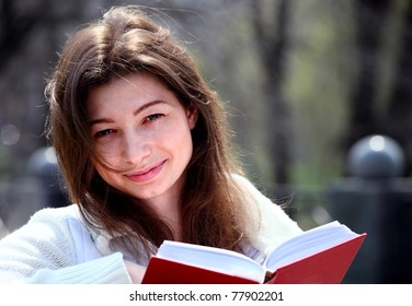 Pretty woman in park reading book and smiling, spring