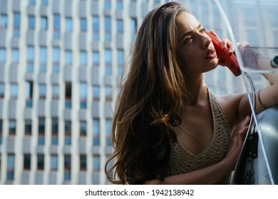 Pretty woman with payphone. Oldfashion town. Vintage concept. Communication. Oldstyled city