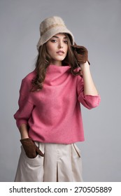 Pretty woman in pink sweater posing on grey background