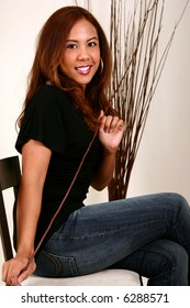 pretty woman playing with tree branch and smiling