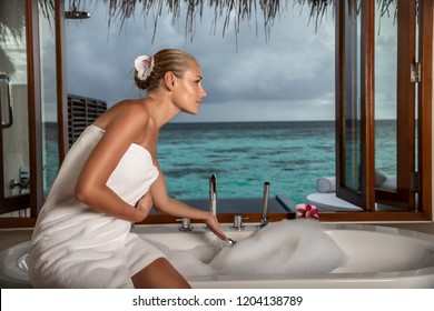Pretty woman with pleasure spending summer vacation on luxury beach resort, enjoying day spa, taking bath with beautiful sea view