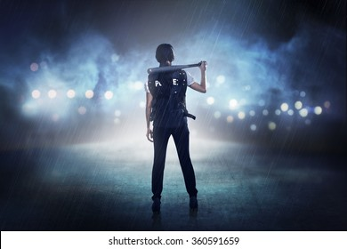 Pretty woman in police vest holding baseball bat as weapon