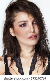 Pretty woman portrait with wet hair and smudged makeup looking aside