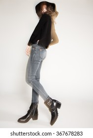 pretty woman posing in denim pants and boots and black hat - intentional motion blur