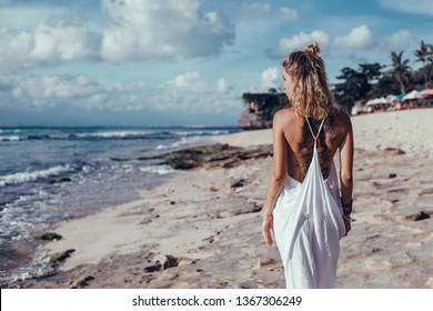 pretty woman posing in the sea, blue sky, hair wild, victory hand up!, outdoor portrait hipster, fashion model, pretty female, denim shorts, hippie, tattoo, hipster girl, Amsterdam, denim shorts,cute