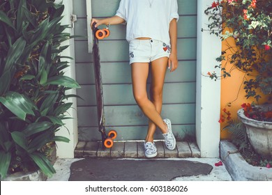 pretty woman posing wit longboard in a street