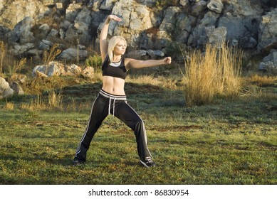 Pretty woman practicing exercise tai chi, kung fu or yoga in natural park