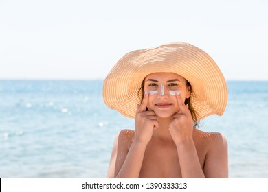 Pretty woman protects her skin on face with sunblock at the beach.