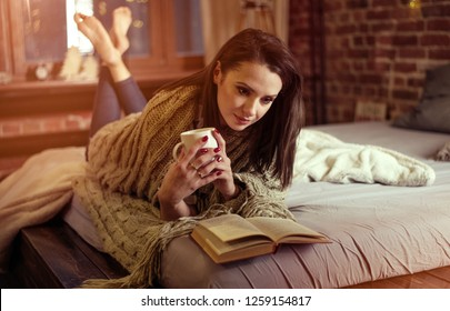 Pretty woman reading a book and holding a mug in the bedroom