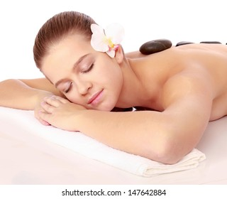 Pretty woman receiving a therapy with hot stones in spa center