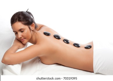 pretty woman receiving a therapy with hot stones in spa center over white